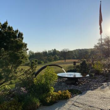 Gartenneugestaltung mit Natursteinsitzplatz und Wasserspiel